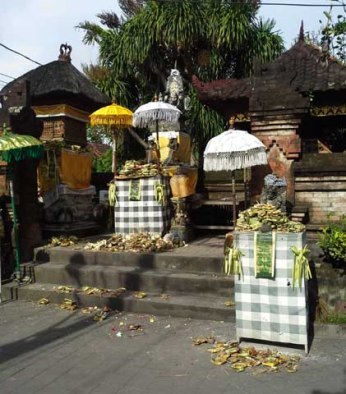 Offerings in front of a temple. Note black and white sash denoting evil and good